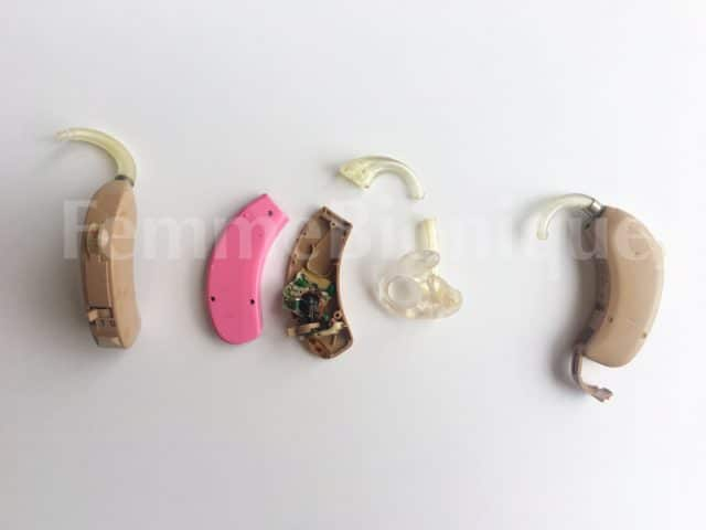 Photos de trois vieux appareils auditifs. Celui du milieu est entièrement démonté.