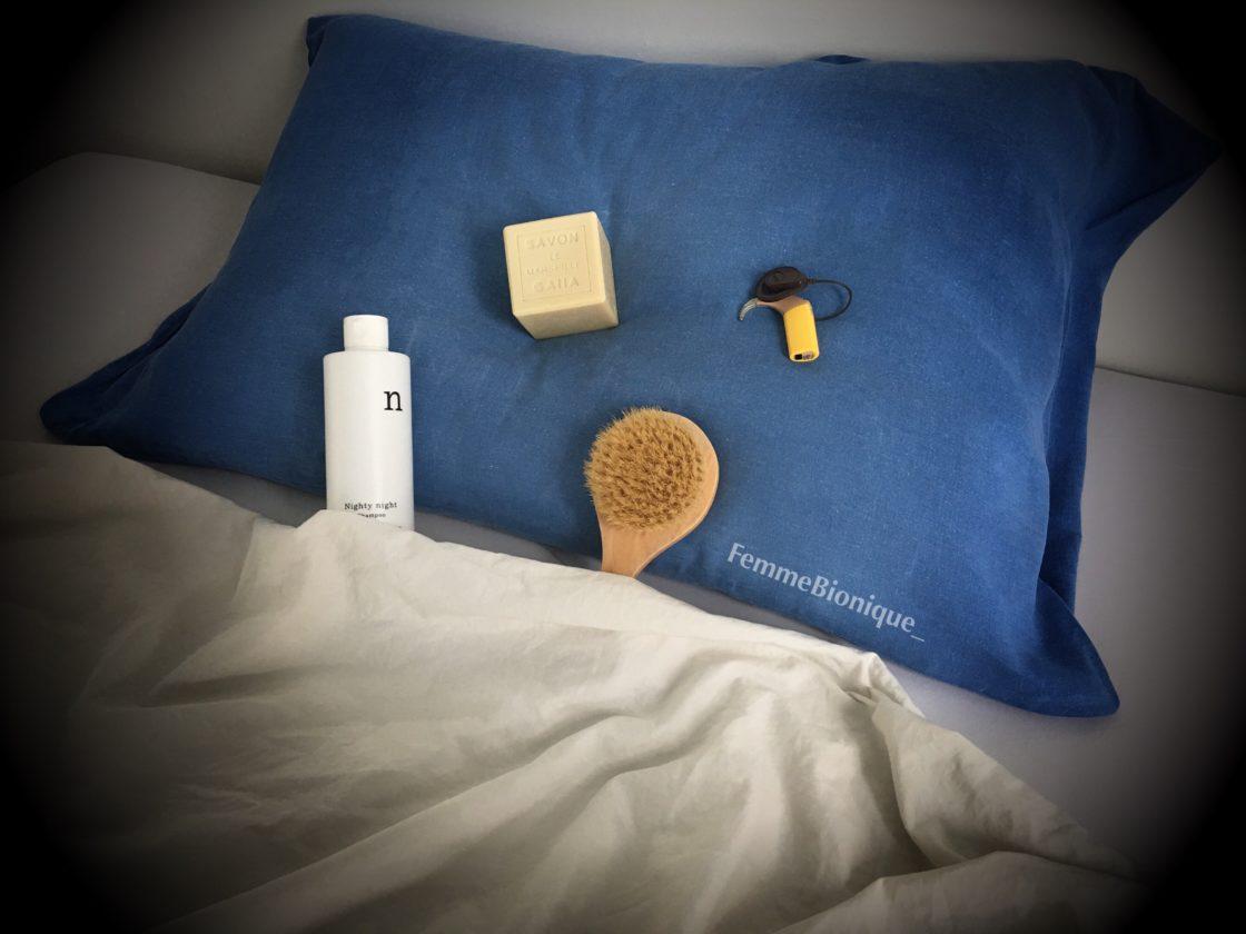 Description de la photo. Photo où l'on voit du savon, une bouteille de shampoing, une brosse et un implant cochléaire couchés dans un lit avec un oreiller bleu. La brosse et le shampoing sont bordés bien confortablement, prêts à dormir ! Fin de la description de la photo.