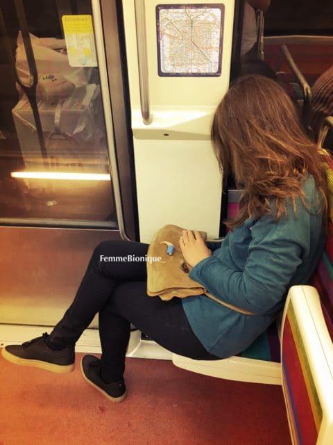 Photo d'une femme qui dort dans le métro avec son implant cochléaire posé sur son sac à main. Bon en vérité ça ne m'arrive jamais de le tenir ainsi, c'est juste pour illustrer l'article !