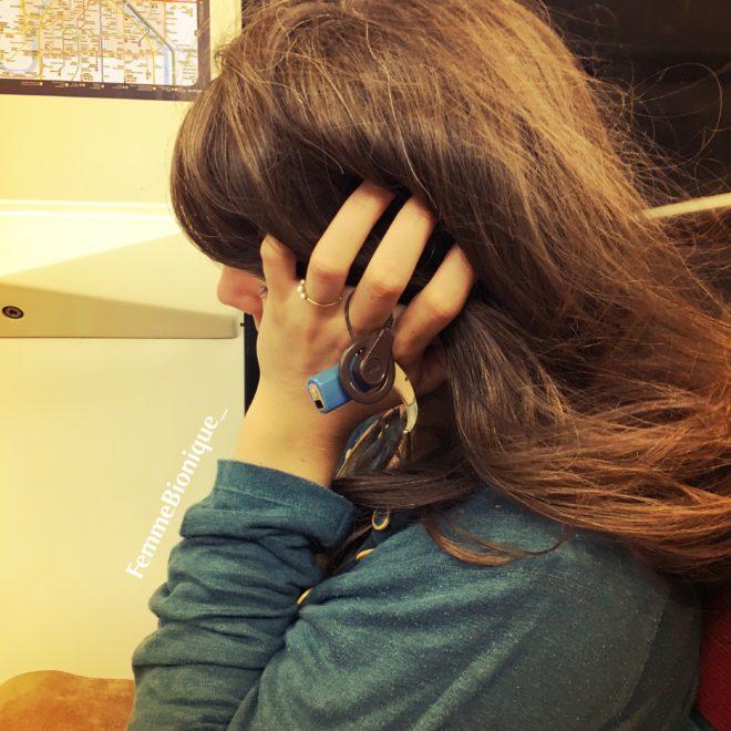 Description de la photo. Photo d'une femme qui dort dans le métro avec son implant cochléaire dans la main. Bon en vérité ça ne m'arrive jamais de le tenir ainsi, c'est juste pour illustrer l'article ! Fin de la description de la photo.
