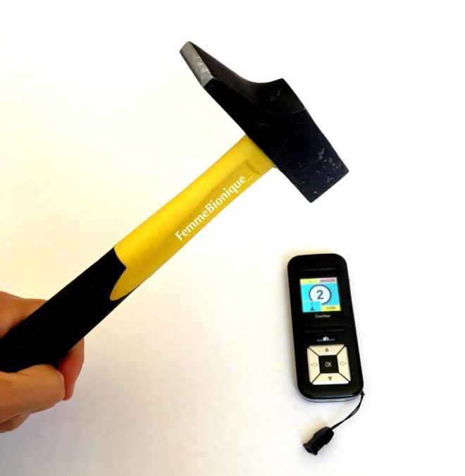 Description de la photo. Photo d'un marteau qui va cogner une petite télécommande d'un implant cochléaire. Fin de la description de la photo.