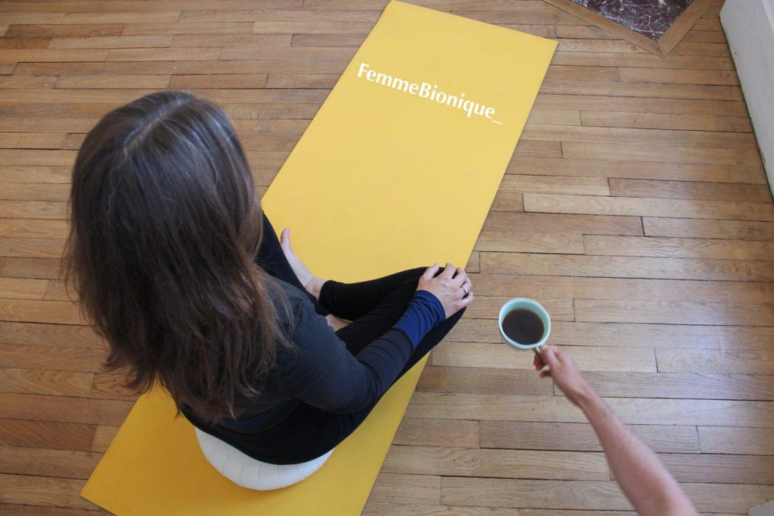 Description de la photo. Photo où l'on voit une femme méditer sur un tapis de yoga avec un café à côté d'elle. Ce café est attrapé par une main d'homme qui le lui pique ! Fin de la description de la photo.