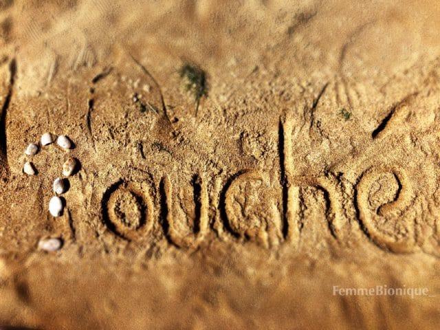Photo d'un texte sur le sable. Un point d'interrogation formé de galets suivit des lettres en sable o-u-c-h-é.