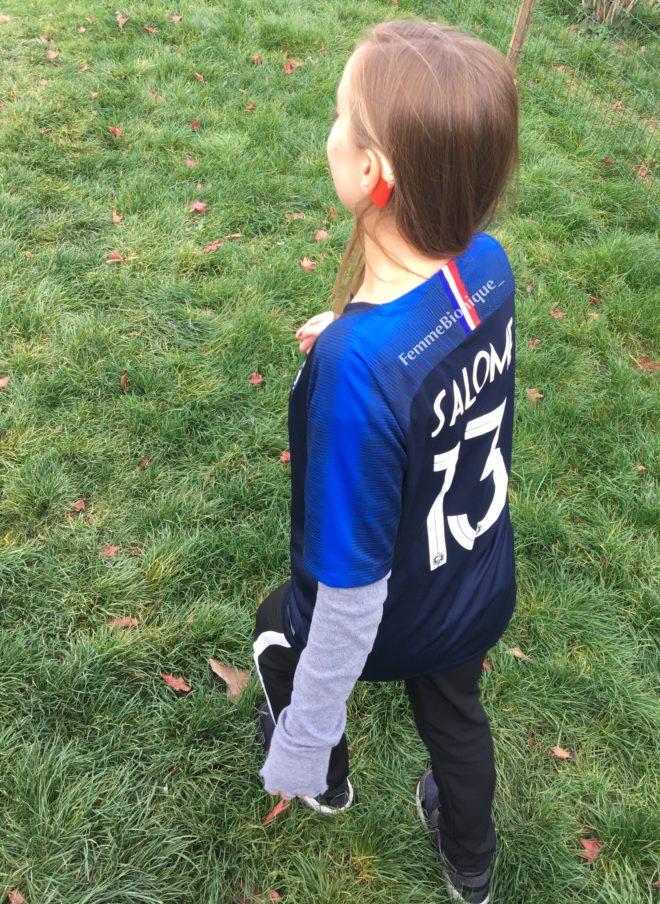 Description de la photo. Jeune femme jouant au foot. Elle porte un implant cochléaire rouge-orangé et un maillot de foot des bleus. Fin de la description de la photo.