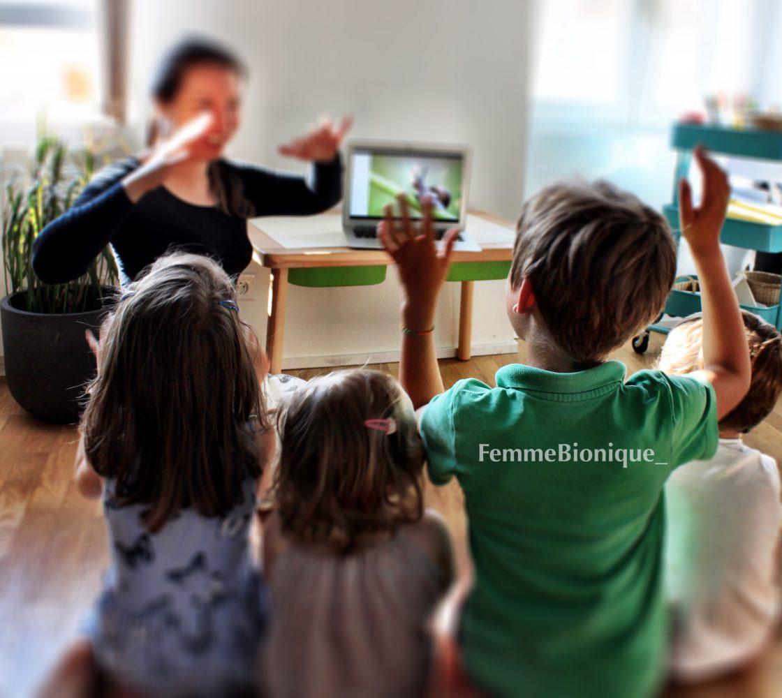 """Description de la photo. FemmeBionique signe le mot """"pluie"""" en Langue des Signes Française, les 4 enfants l'imitent. Fin de la description de la photo."""