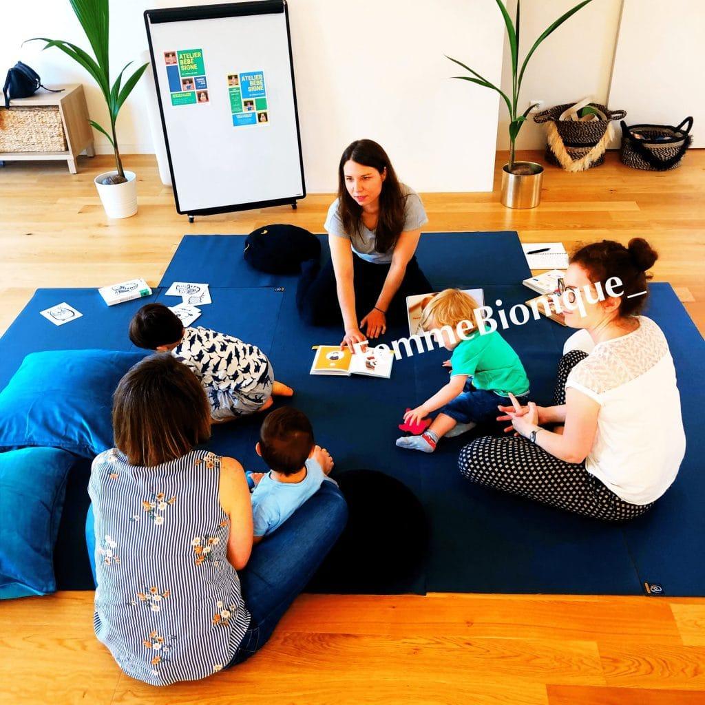 Début de la description de la photo. 3 adultes et 3 enfants de 2 et 3 ans assis par terre avec des livres pendant l'atelier Bébé Signe. Fin de la description de la photo.