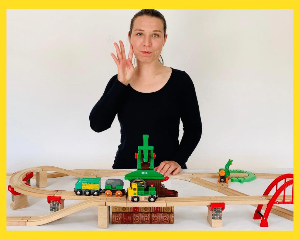 """Début de la description de la photo. FemmeBionique en train de signer """"femme"""" parmi un décor de trains en bois. Fin de la description."""