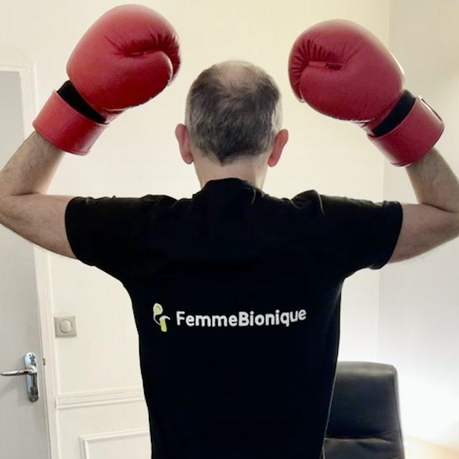 Début de la description de la photo. Un homme de dos portant un T-shirt avec le logo de FemmeBionique, les bras levés avec des gants de boxe. Fin de la description.