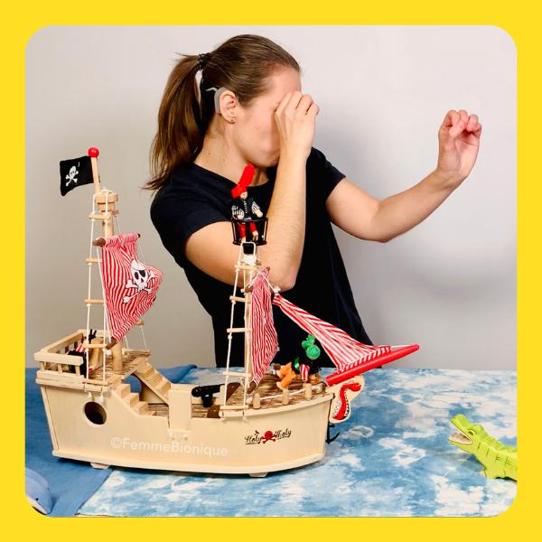 Début de la description de la photo. Clara mime le geste de regarder à travers une longue-vue. Sur la table, un bateau de pirates. Fin de la description.