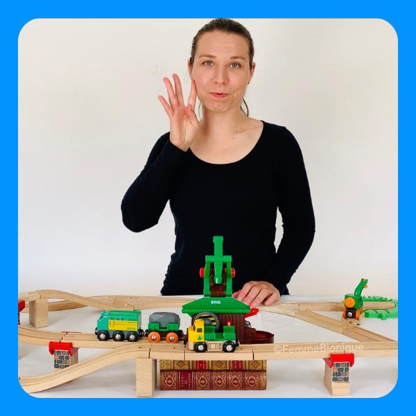 """Début de la description de la photo. Clara signe le mot """"femme"""". Sur la table, des jouets de train. Fin de la description."""