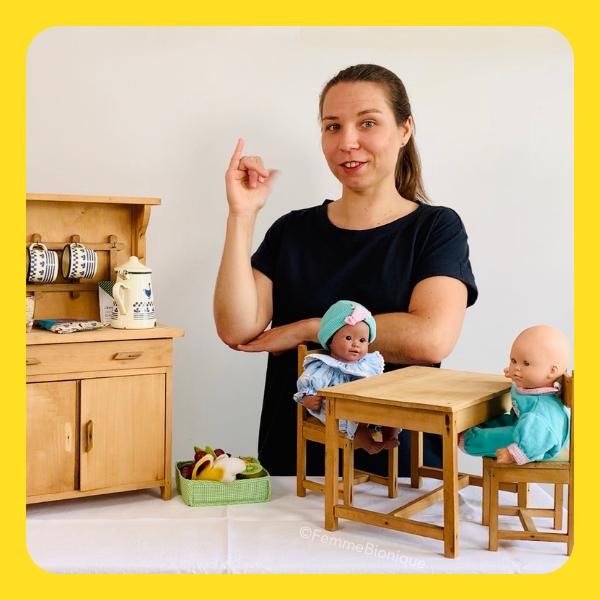 """Début de la description de la photo. Clara signe le mot """"poupée"""". Sur la table, des poupées avec des meubles de cuisine de poupée. Fin de la description de photo."""