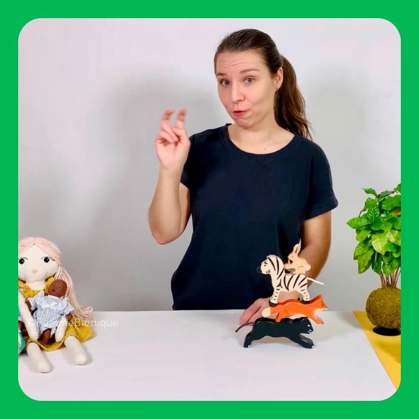 """Début de la description de la photo. Clara signe """"vert"""" dans un décor avec des animaux en bois et des poupées. Fin de la description."""